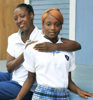 Raquel Dillon with her daughter, Geraldlynn, who wears a KIPP school uniform. Dillon hoped the school's focus on academics—maintained through chants, finger snapping, and strict enforcement of rules— would give her daughter opportunities she'd lacked. Dillon's faith faltered as the school's culture failed to connect with students. Photo by Susan Poag Photography.