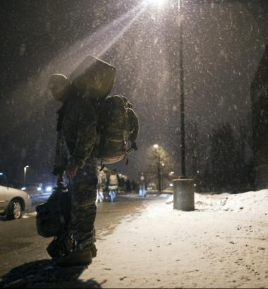 Army Spcs. Frank Casillas waits for a ride home outside Fort Drum, New York's Magrath Gymnasium in March 2011 after a yearlong deployment in Afghanistan. (Redux)