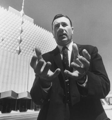 Oral Roberts, an early champion of the prosperity gospel, stands before the Tulsa, Oklahoma, headquarters of his ministry, the Abundant Life Building, in 1962. (Time & Life Pictures / Getty Images)